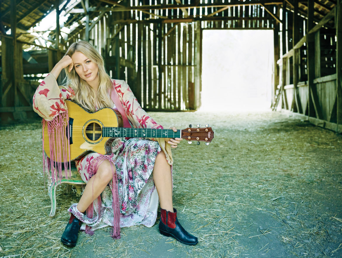 Jewel on chair in a barn with guitar