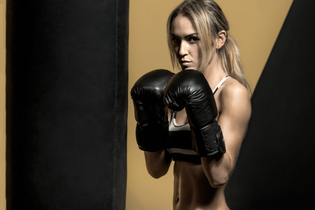 young boxer woman in boxing gloves with punching bag